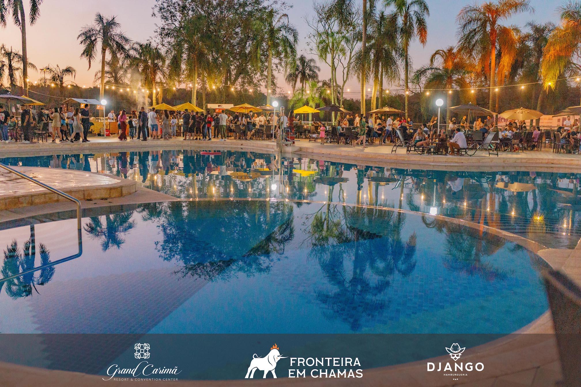 Pátio da Piscina do Grand Carimã Resort, iluminado por um varal de luzes durante o Fronteira em Chamas